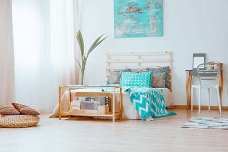 furniture design: Notebooks with patterned covers on the wooden shelf standing next to a bed