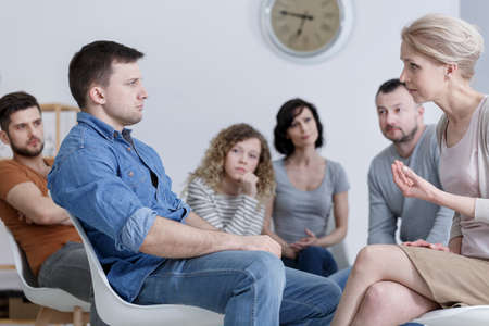 Therapist speaking to a man during group counseling session Stock Photo