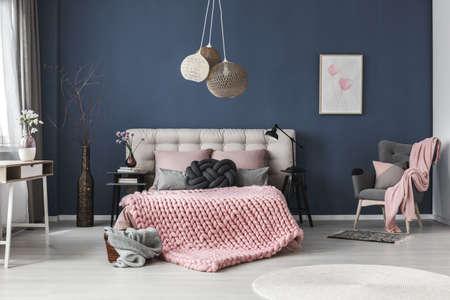 Chambre spacieuse et lumineuse avec des décorations mignonnes et une affiche accrochée à un mur sombre