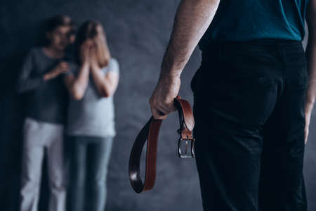 Abused children terrified of their father holding a belt