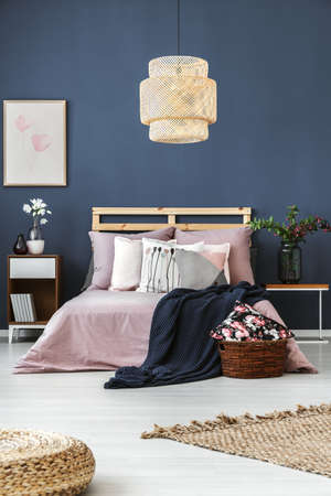 Donkere ommuurde ruimte met decoratieve kussens en blauwe deken op houten bed