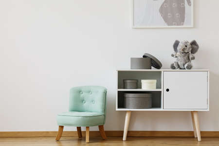 Bright cupboard standing next to mint chair for children