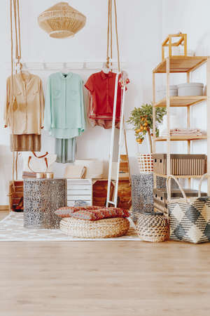 Creative modern wardrobe with colorful clothes in the room with wicker decorations Stock Photo