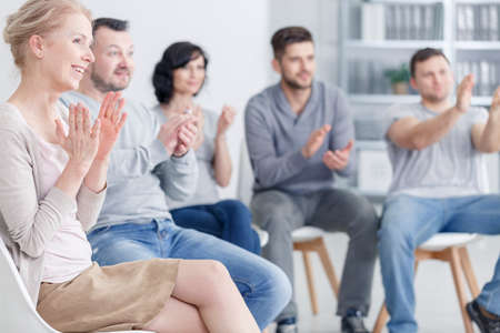 Happy people clapping at support group meeting Stock Photo