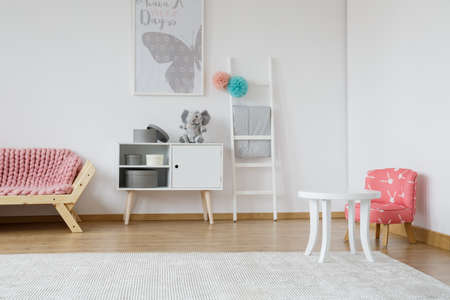 Kid room with small white table and rabbit patterned red chair Stok Fotoğraf - 82361386
