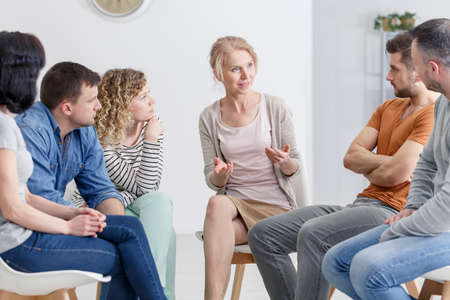 Psychologist encouraging her patients to open up at group meeting Stok Fotoğraf - 82361384