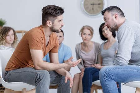 Twee volwassen mannen tijdens psychologische training in groep Stockfoto