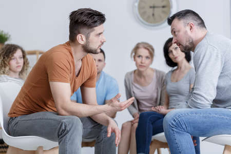 Two adult men during psychological training in group Standard-Bild