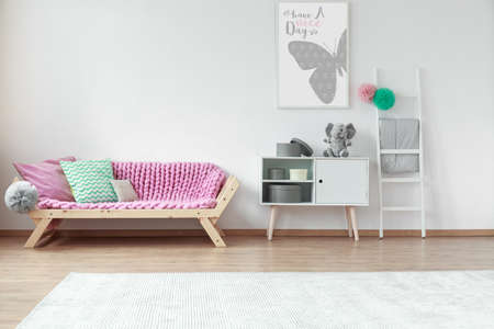 Colorful cushions lying on a wooden pink couch in kid room with poster