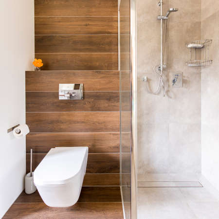 Modern bathroom with wood decor with toilet and glass travertine shower