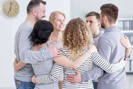 People having group hug during therapy in rehab Stock Photo - 82361503