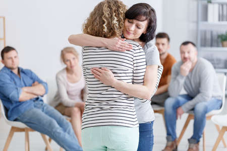 Concerned woman comforting another woman in support group