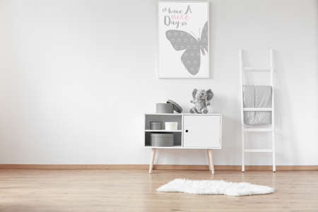 Witte houten kast met ronde kartonnen dozen en zacht vloerkleed in de kamer