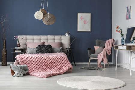 部屋の隅のクッションとピンクの毛布と暗い灰色の快適なアームチェア 写真素材
