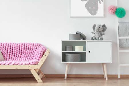 白い食器棚の横にピンクの柔らかい毛布立って木製ソファ