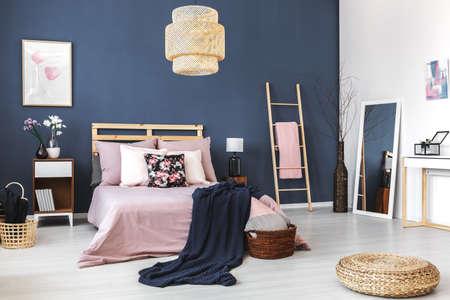 Big white mirror standing in the corner of cozy bedroom