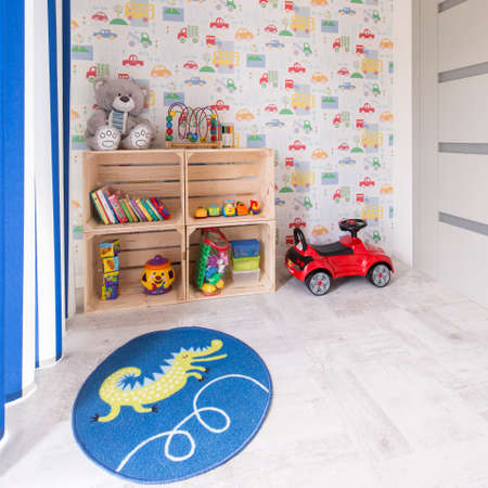 Childrens room with dragon carpet, car wallpaper and wooden boxes as eco-friendly shelfs for toys Stok Fotoğraf