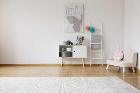 白いキャビネットと快適なソファ付きの明るい広々 とした子供部屋 写真素材