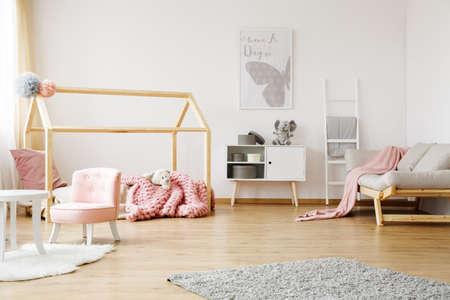 Espaciosa habitación totalmente amueblada chica con cama creativa y sofá luminoso Foto de archivo - 82361819