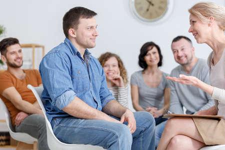 Glimlachende man raadplegen bij zijn psychotherapeut tijdens de groepstherapie sessie Stockfoto