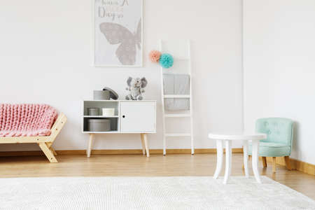 Wooden pink couch and small mint chair in baby room with poster Stockfoto