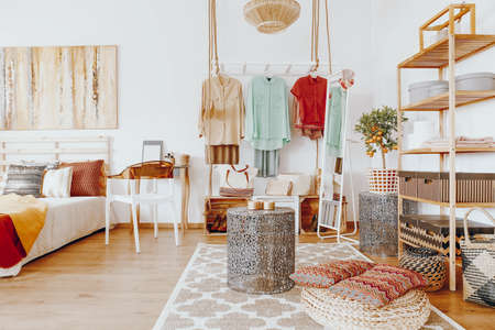 furniture design: Bright spacious room with colorful clothes and decorations in boho style Stock Photo