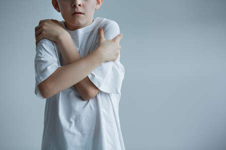 Scared boy in white t-shirt - conceptual photo