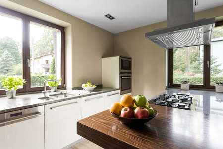 Modern kitchen with wooden kitchentop and vent Banco de Imagens - 82489791