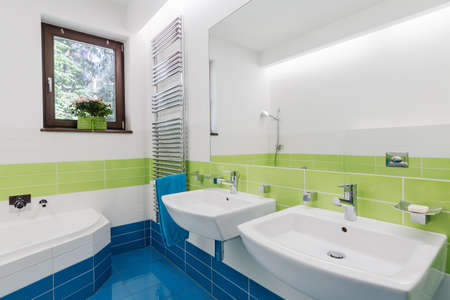 Colourful bathroom with bathtub, large mirror and two sinks Stock Photo