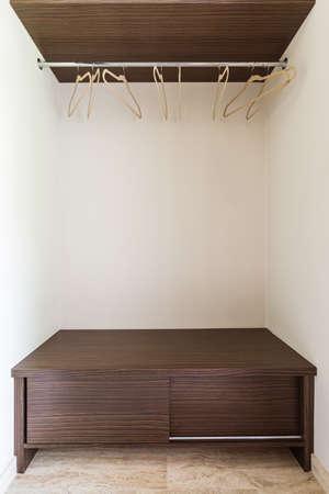 Empty wooden garderobe with few hangers Stock Photo