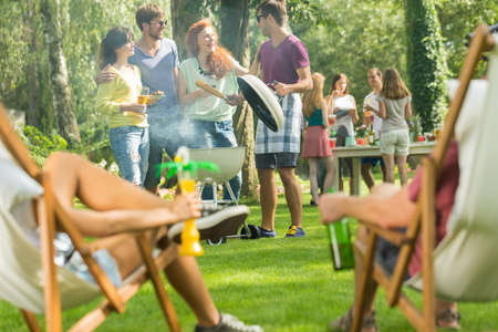 Young people having good time at casual garden party Stock Photo