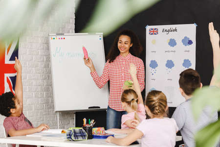 Young teacher learning kids basic words in english Foto de archivo