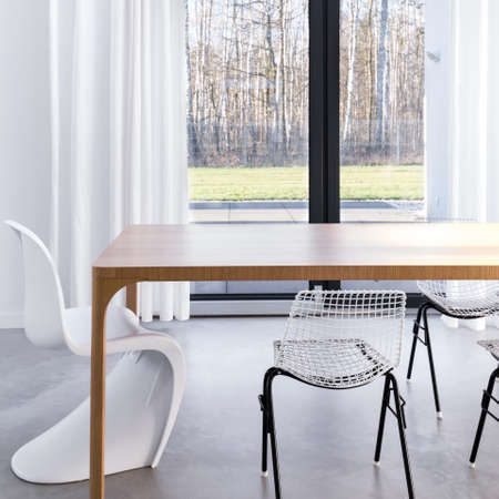 Scandinavian style dining room with dining table, stylish chairs and garden view through terrace window Stock Photo - 82489953