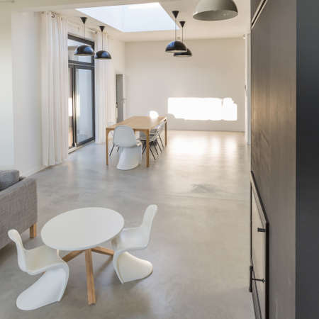 Spacious dining room in modernist style with white wooden tables and chairs with simple concrete floor
