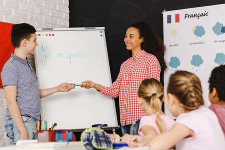 Jonge jongen door het witte bord tijdens de Franse lessen Stockfoto - 82490023
