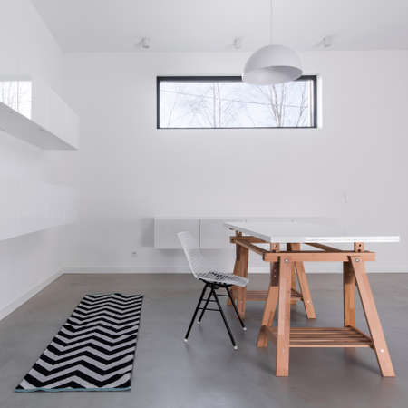 Raw simple decor of spacious dining room with modernist table, stylish chair and patterned carpet Stock Photo