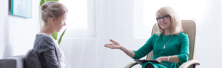 Middle-aged blonde woman sitting during psychotherapy with female therapist