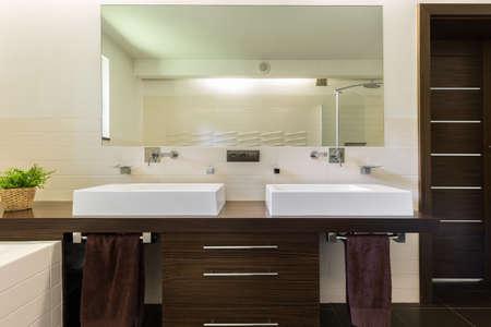 ダークブラウンの家具とモダンなバスルームは、白流しし、タオル 写真素材