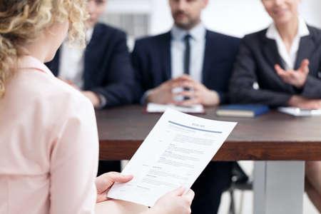 就職の面接の間に彼女の履歴書を保持している女性