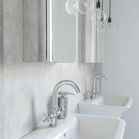 bathroom design: Two sinks in concrete bathroom with simple cabinets with mirrors Stock Photo