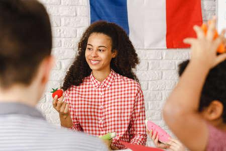 아이들과 함께 프랑스어 수업을 이끌고 행복한 젊은 여자 스톡 콘텐츠