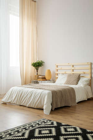 Beige and white minimalist bedroom for young hipster Foto de archivo