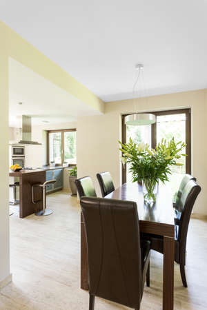 Beige dining room with table and leather chairs open to the kitchen Banco de Imagens