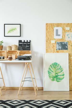 Artists workspace with simple wooden furniture and paintings