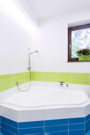 Bathroom with colourful tiles, bathtube and window