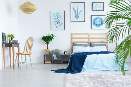 Decorated white bedroom in stylish contemporary scandinavian apartment Stock fotó