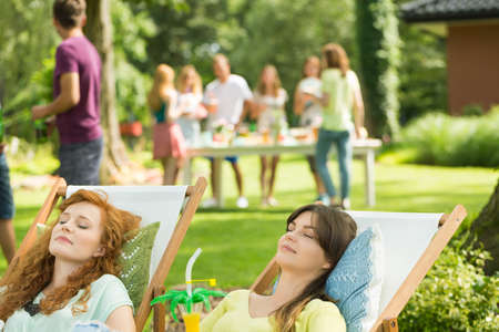 Women with drinks sunbathing during casual garden party
