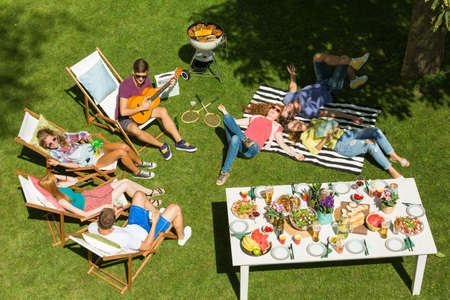 Group of friends chilling during bbq party in the countryside Stock Photo