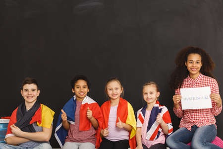 Young kids different flags sitting next to teacher Stockfoto