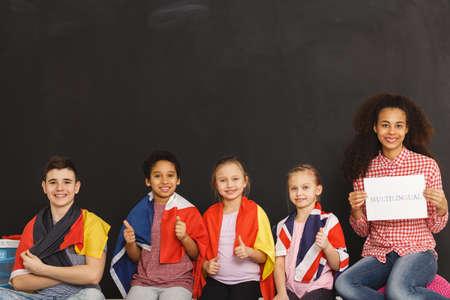 Young kids different flags sitting next to teacher Foto de archivo